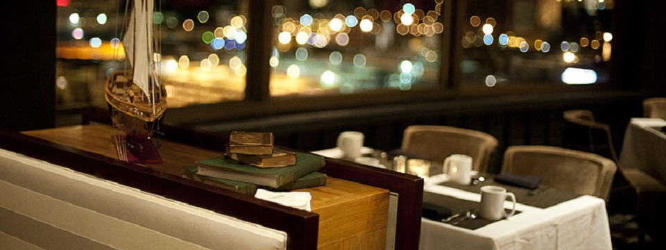 Hotel restaurant with tables covered in white linen and books and ship decor