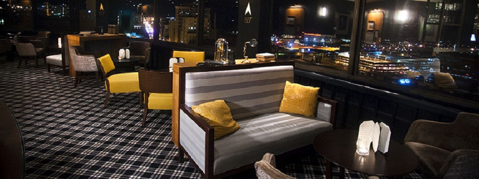 Lounge seating area with gray couches, yellow chairs and a city view
