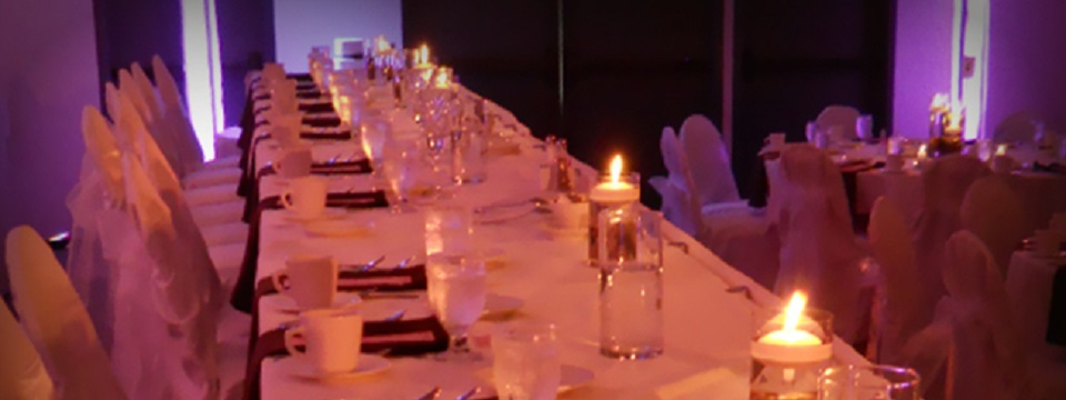 Reception table covered in white linens with candles, water glasses and coffee cups