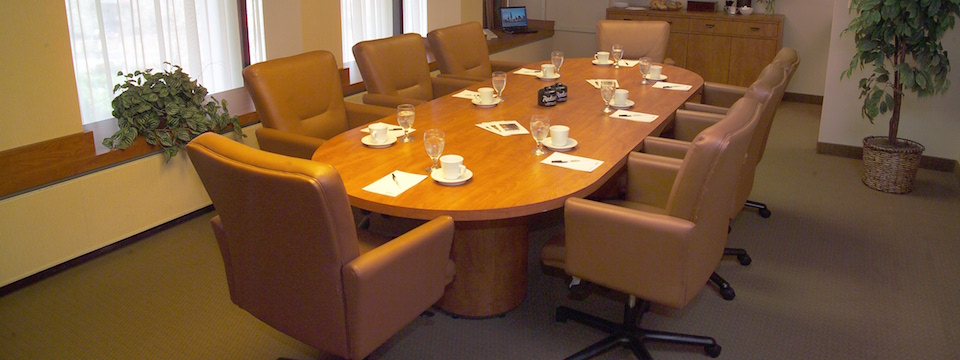 Hotel boardroom with eight leather chairs around a large table