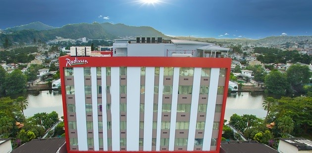 Exterior view of Radisson Hotel Guayaquil with mountains in the distance