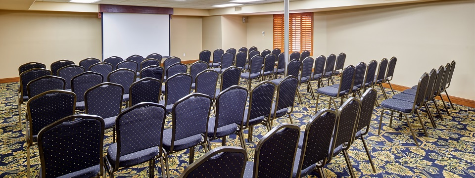 Meeting room with rows of chairs lined up in front of a projector screen