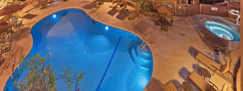 Evening view of outdoor pool, hot tub and lounge chairs