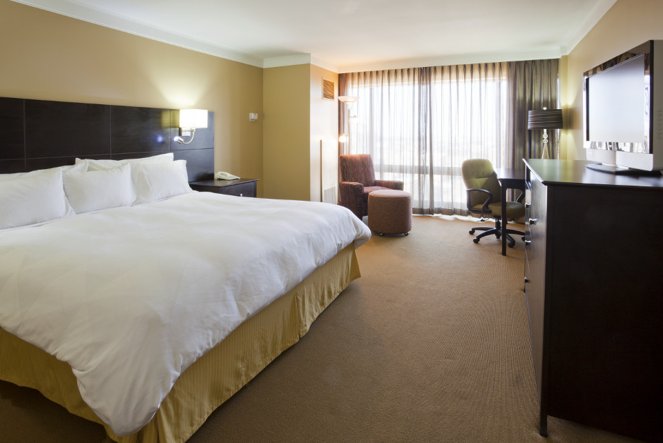 Spacious hotel room with king bed and work desk