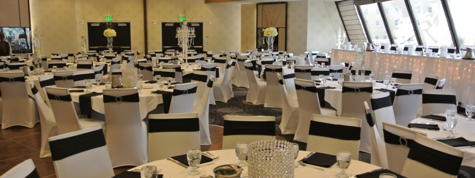 Head table facing numerous round tables in hotel ballroom