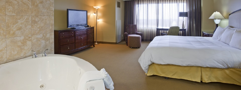 Whirlpool tub, flat-screen TV and king bed in hotel suite