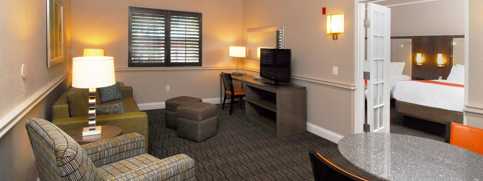 Hotel suite living room with seating and dining areas