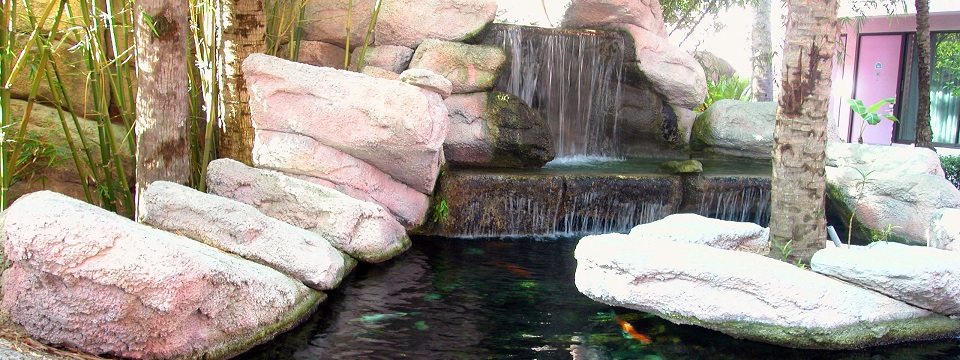 Hotel's outdoor waterfall feature with fish pond