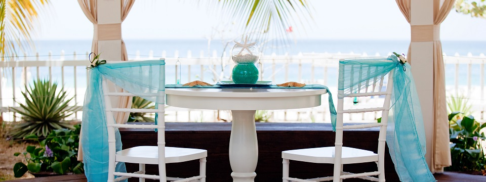 Beach resort balcony with tables set for wedding reception