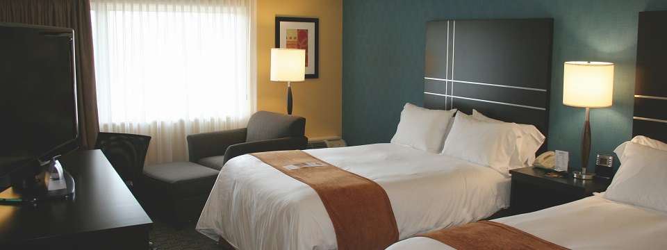 Hotel room with two queen beds and chair with ottoman