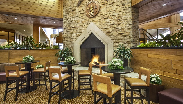 Hotel Lobby With A Stone Fireplace And Tables Fl Accents