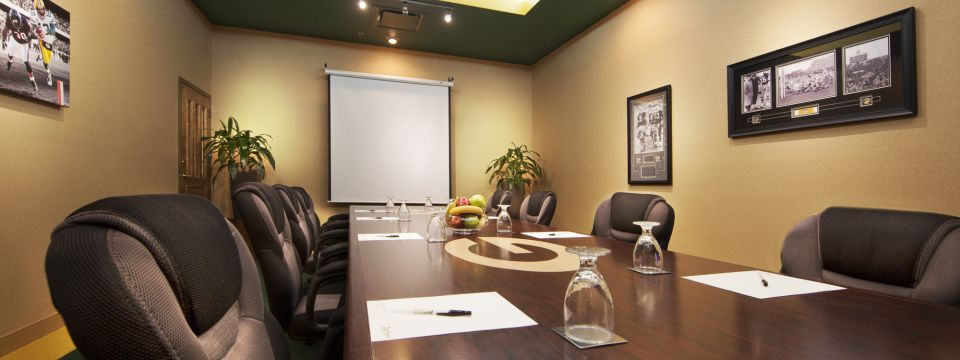 Boardroom with a projector screen and a long table surrounded by black chairs