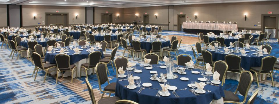 Banquet space with clusters of round tables surrounded by chairs in Green Bay