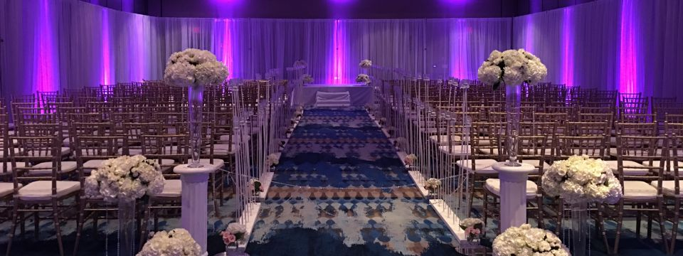 Wedding ceremony in hotel event space with purple lighting and white flowers