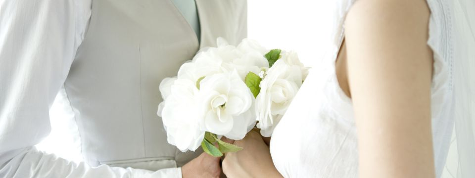Newlywed couple holding a white bouquet