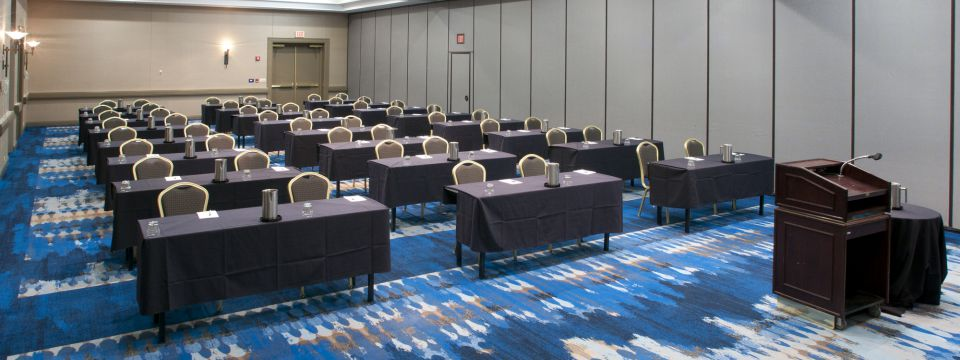 Meeting space with a patterned carpet and rows of tables and chairs facing a lectern