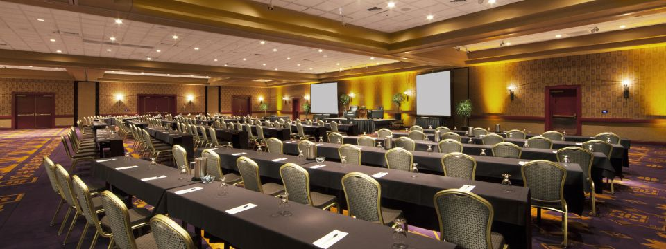 Event venue with rows of tables and chairs facing two projector screens