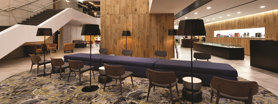 Modern hotel lobby with a patterned rug and plush seating