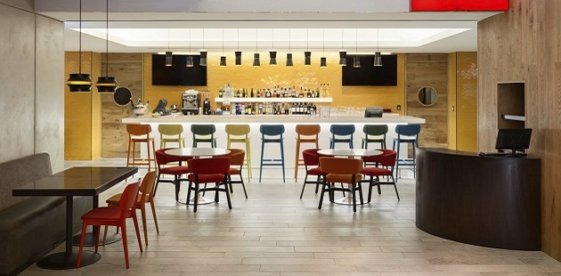 Hotel's restaurant with colorful chairs and a large bar