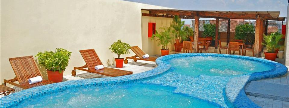 Hotel's terrace with a hot tub and wooden furniture