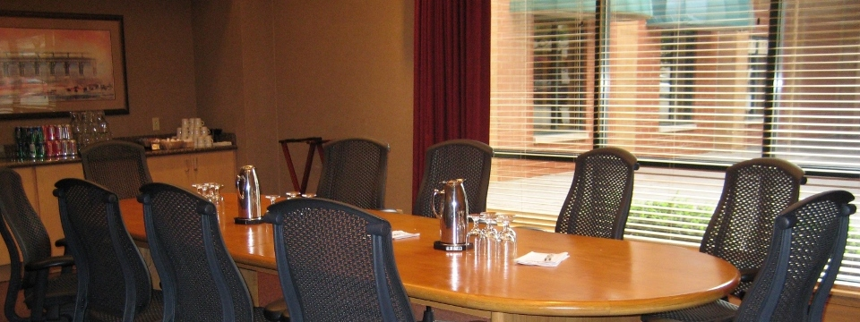 Boardroom with oval table surrounded by chairs