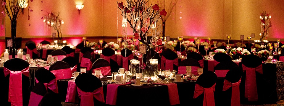 Pink and black decorated wedding tables with floral arrangements
