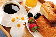 Coffee and orange juice paired with fresh berries and croissants