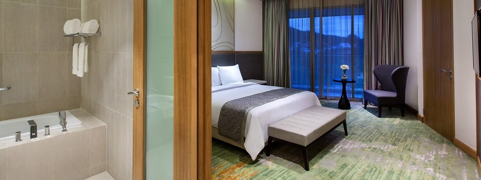 Hotel suite with a spacious bathroom, a king bed and a modern armchair