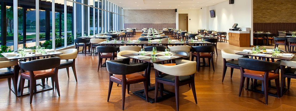Batam hotel restaurant with clusters of tables and chairs and large windows