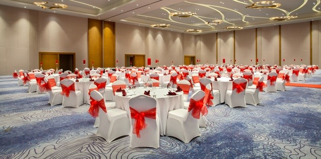 Meeting space with clusters of round tables surrounded by chairs with red bows