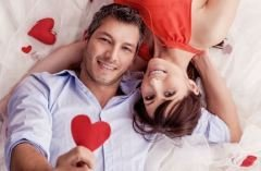 Young couple lying down holding red paper hearts