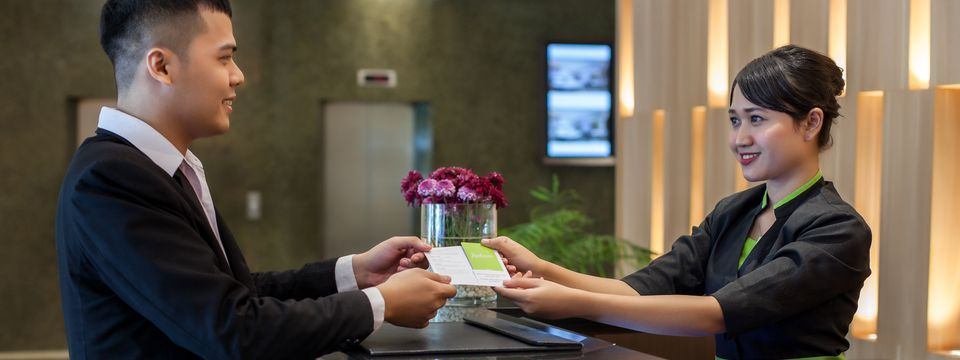 Hotel guest checking in at welcoming reception desk