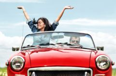 Couple riding in a red convertible