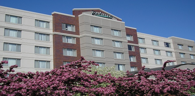 Exterior of the Radisson with pink and white flowers in bloom