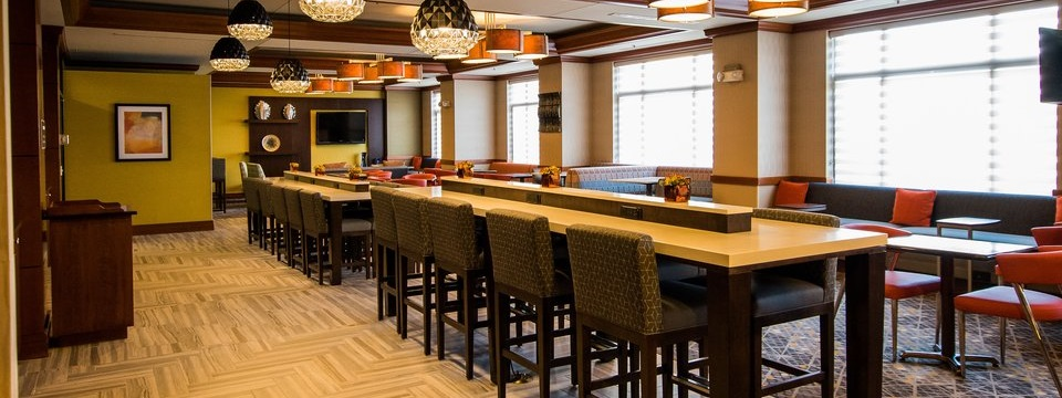 Hotel dining area with stools, countertop seating and modern light fixtures