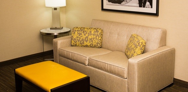 Guest room living area with a tan couch, two yellow accent pillows and a yellow ottoman
