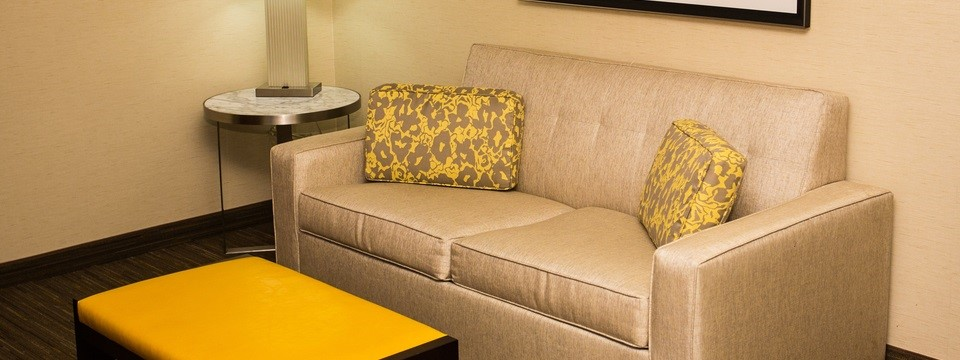 Suite living area with beige walls, a tan couch and a yellow ottoman