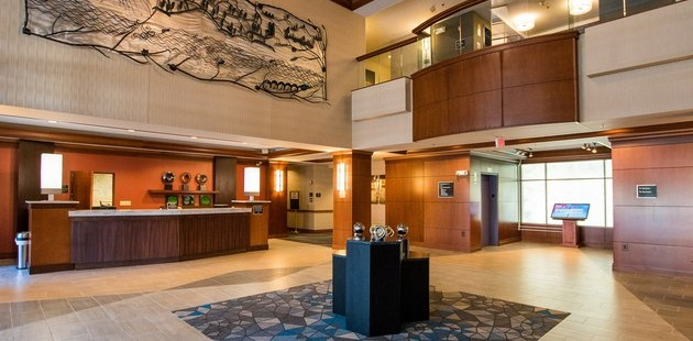 Modern lobby and front desk with wooden accents and patterned tile floors