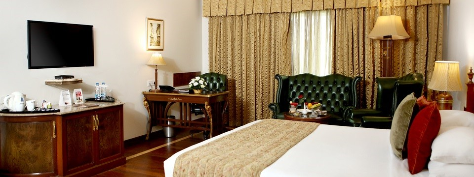 Guest room featuring queen bed, work desk and green leather sofa