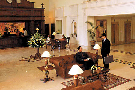 Spacious lobby with front desk area, seating and flower arrangement