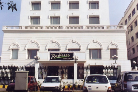 Exterior of Radisson Jalandhar with white building and parked cars