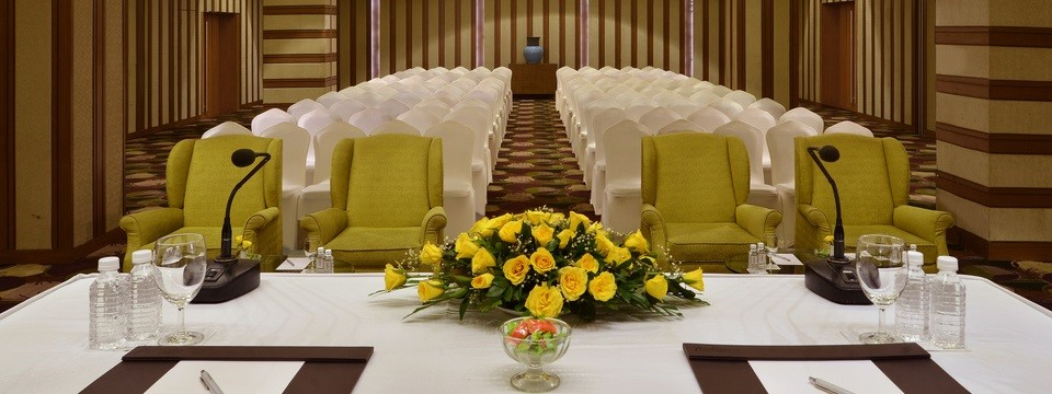 Meeting room with a head table, four armchairs and rows of white chairs