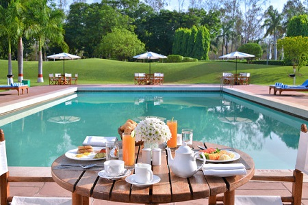 Outdoor pool with table filled with food beside it