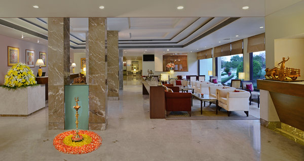 Khajuraho hotel's lobby with seating and elegant columns
