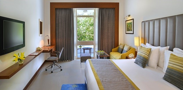 Khajuraho hotel room with large bed, TV and glass door