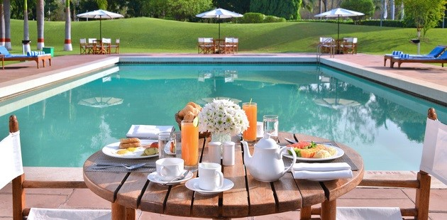 Table filled with food by outdoor pool