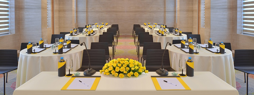 Event space featuring round tables and a head table with yellow roses