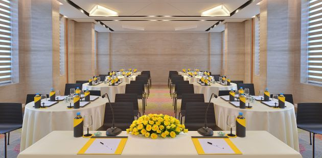 Meeting room featuring round tables and a head table with yellow flowers