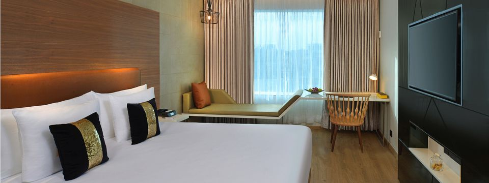 Spacious guest room with one bed, a chaise lounge and a flat-screen TV