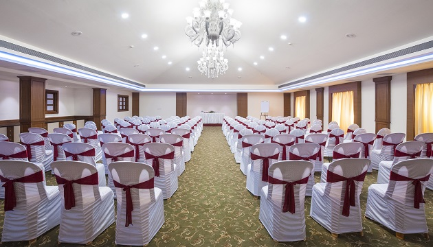 Meeting room featuring white chairs with red accent bows